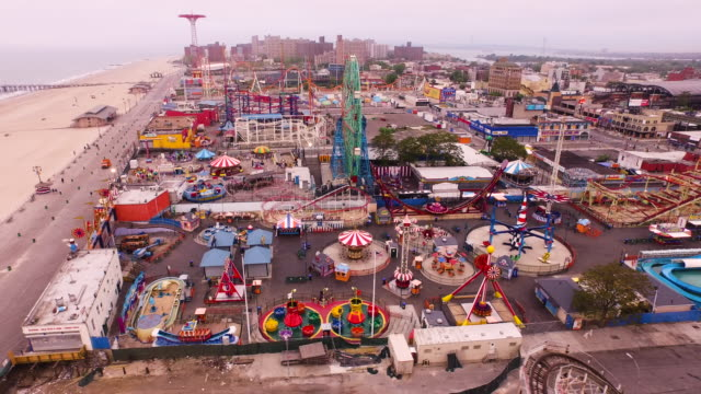 aerial flying across coney island, beach and atlantic ocean in brooklyn, new york city - coney island stock-videos und b-roll-filmmaterial