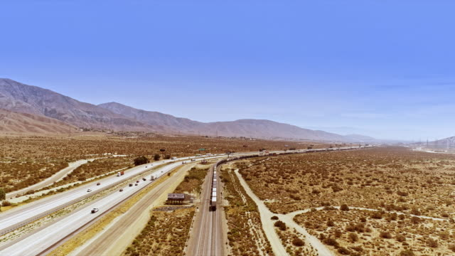 ws aerial flying across interstate 10 california freeway as mile-long freight train runs parallel to the highway and a frontage road all traveling east towards coachella valley in far distance - interstate 10 stock videos & royalty-free footage