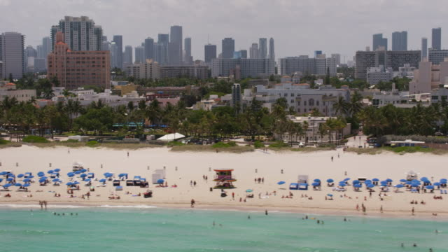aerial flying across south beach, beautiful sunny day miami fl - beach umbrella stock videos and b-roll footage