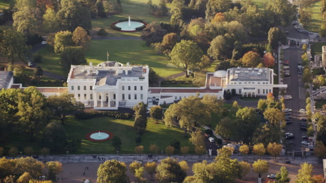 aerial flying across the white house north lawn, daytime dc - la casa bianca washington dc video stock e b–roll