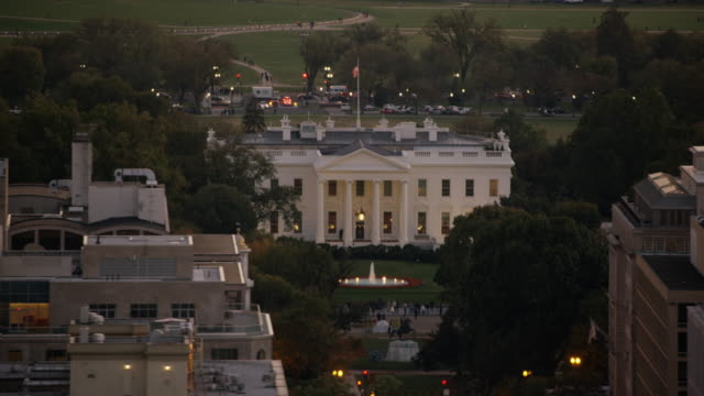 aerial flying across the white house north lawn, sunset dc - la casa bianca washington dc video stock e b–roll