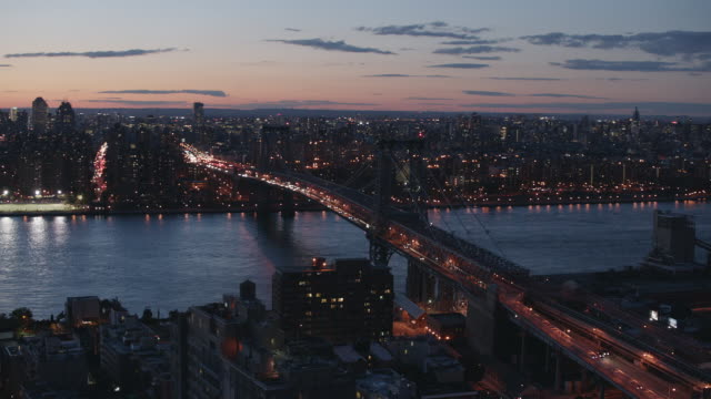 Aerial flying across the Williamsburg Bridge from Brooklyn with Manhattan across at sunset