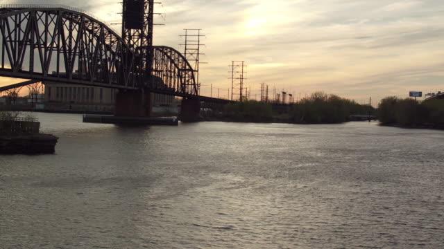 vídeos y material grabado en eventos de stock de aerial flying along the delaware river beside a railroad bridge on a spring afternoon in philadelphia - philadelphia pennsylvania