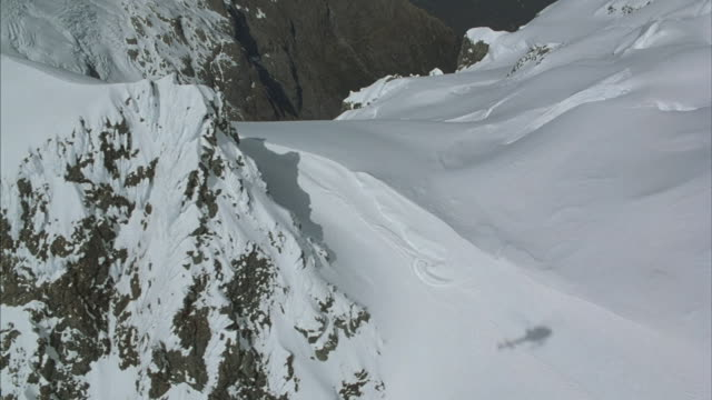 Aerial flying around and down the side of a rugged snow-covered mountain peak.