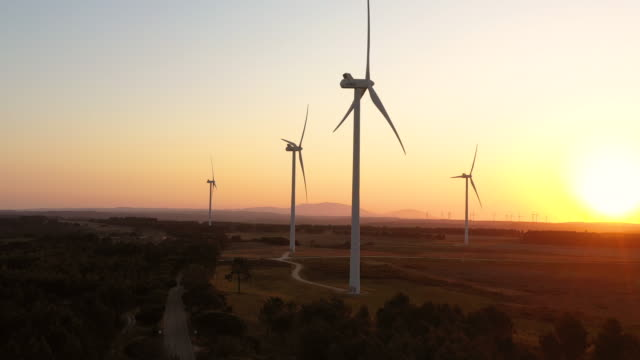 vidéos et rushes de aerial flying around close to a cluster of windmills, wind farm in southern portugal at sunrise - développement durable