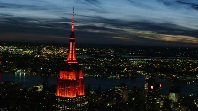 Aerial flying around Empire State Building with red lights on, night USA