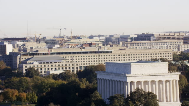 Aerial flying around Harry S. Truman Building, past Lincoln Memorial, Washington DC daytime