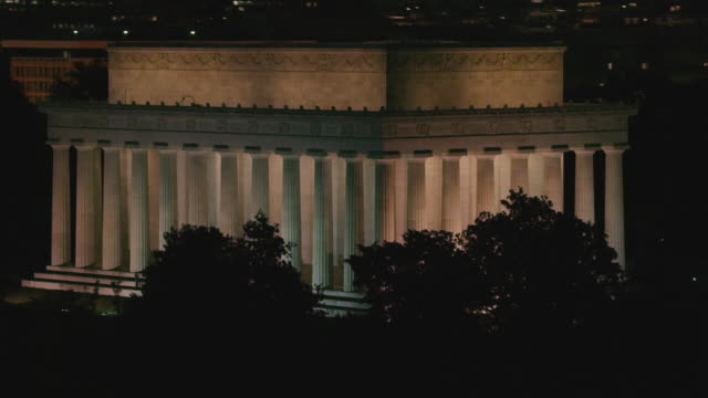 aerial flying around lincoln memorial at night with lights on dc - lincolndenkmal stock-videos und b-roll-filmmaterial
