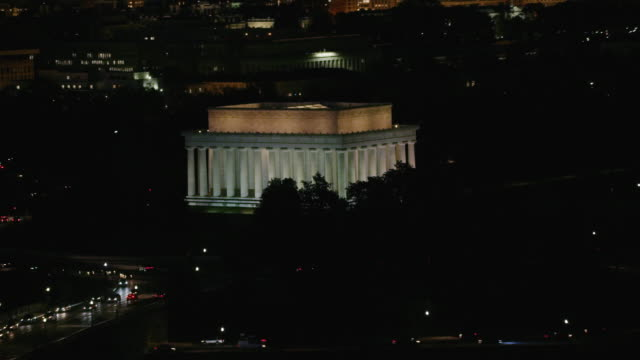 Aerial flying around Lincoln Memorial at night with lights on DC