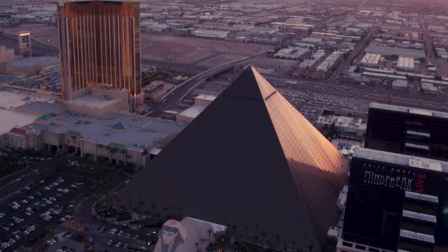 aerial flying around luxor hotel & casino, sunset - pyramid stock videos and b-roll footage