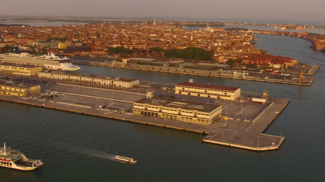 aerial flying around ship docks in central venice city in italy at sunset - darsena video stock e b–roll