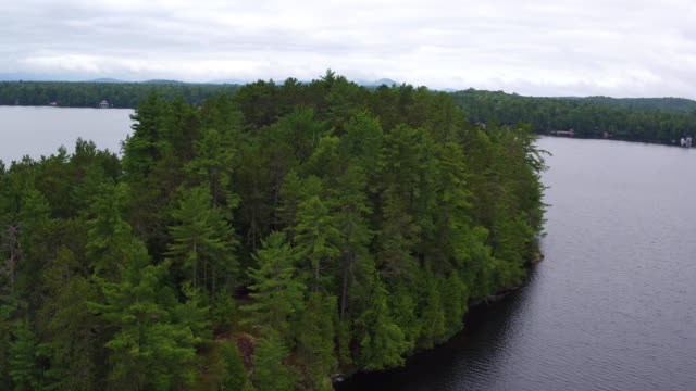 Aerial flying around small island in Saranac lake, afternoon