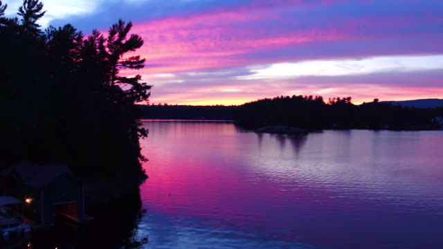 Aerial flying around small island over the water of Saranac lake at sunset