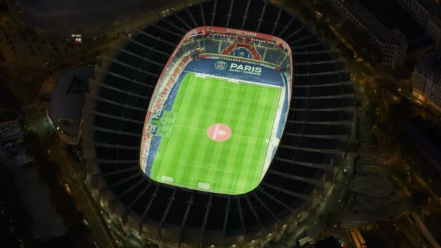 aerial flying around soccer stadium with lights on in paris france, night - stadion stock-videos und b-roll-filmmaterial