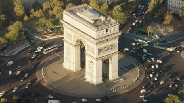 aerial flying around the arc de triomphe in paris france, morning - triumphal arch stock videos & royalty-free footage