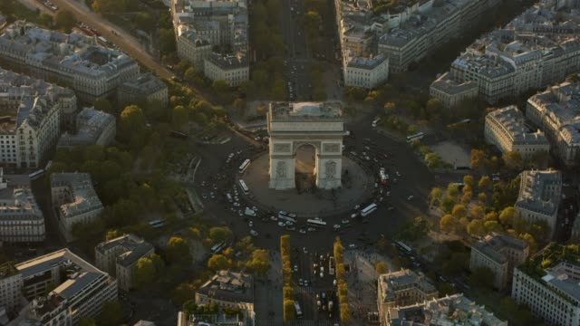 aerial flying around the arc de triomphe in paris france, sunset - arc de triomphe paris stock videos & royalty-free footage