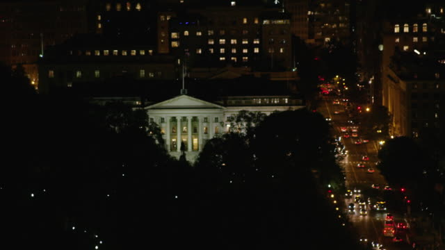 vídeos de stock e filmes b-roll de aerial flying around the department of the treasury at night d.c. - política