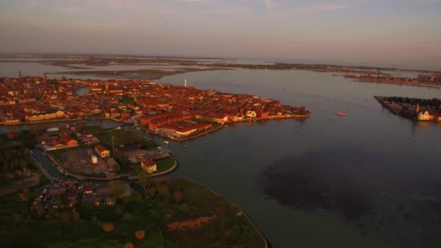 vídeos de stock, filmes e b-roll de aerial flying around the island of murano in venice, italy at sunset - veneziana