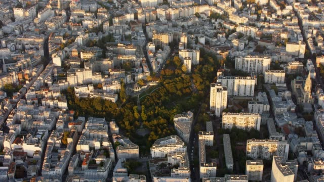 aerial flying around the parc de belleville in paris france, sunset - zoom out stock-videos und b-roll-filmmaterial