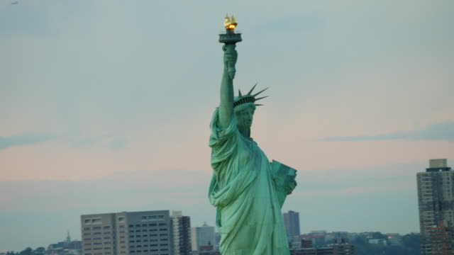 Aerial flying around the Statue of Liberty at sunset
