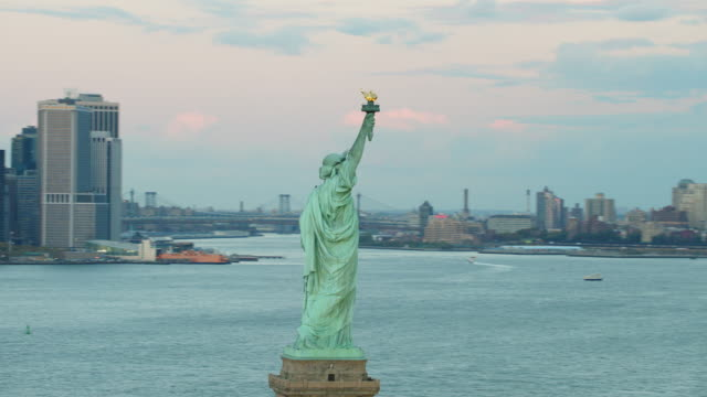 Aerial flying around the Statue of Liberty to reveal the New York City, lower Manhattan behind