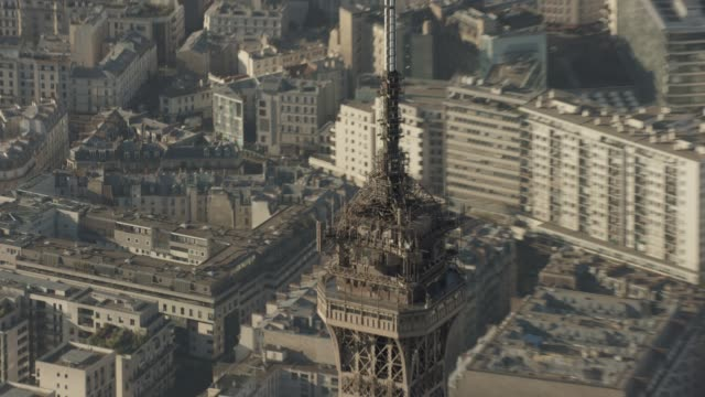 vidéos et rushes de aerial flying around the top of eiffel tower in paris france, daytime - dolly shot