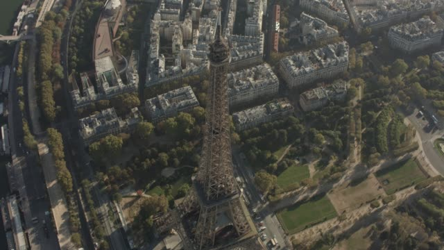 aerial flying around the top of eiffel tower in paris france, daytime - eiffelturm stock-videos und b-roll-filmmaterial
