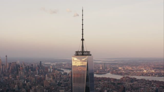 aerial flying around the top of the world trade center to reveal manhattan below, nyc at sunset - one world trade center stock-videos und b-roll-filmmaterial