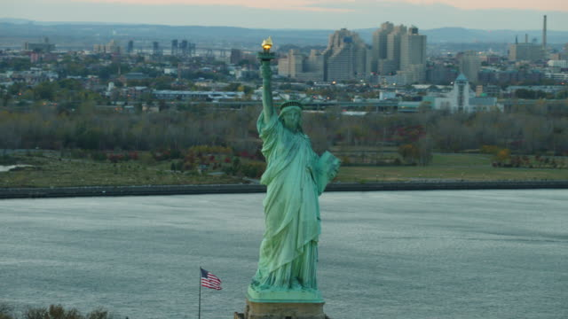 Aerial flying around to the front of the Statue of Liberty at the end of the day