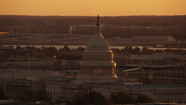 aerial flying around united states capitol, sunset washington dc - capitol building washington dc stock videos and b-roll footage