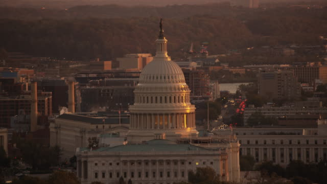 Aerial flying around United States Capitol, sunset Washington DC