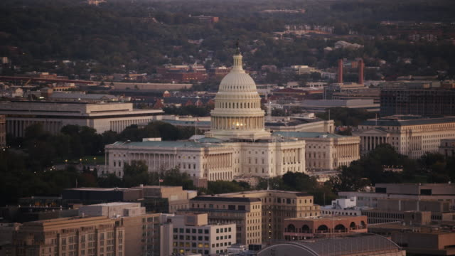 aerial flying around united states capitol, sunset washington dc - politics stock-videos und b-roll-filmmaterial