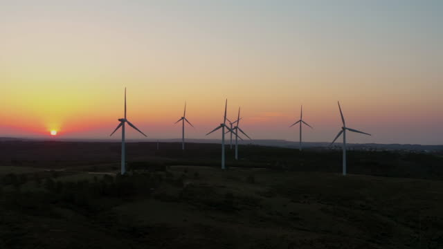 aerial flying away from cluster of windmills, wind farm in southern portugal at sunrise - power in nature stock videos & royalty-free footage