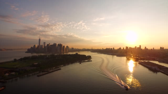 aerial flying away from manhattan over east river and boat at sunrise - east river stock videos & royalty-free footage