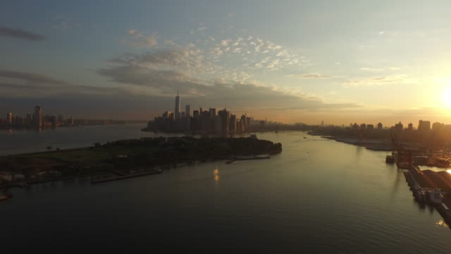 aerial flying away from manhattan over the east river at sunrise - ニューヨーク湾点の映像素材/bロール