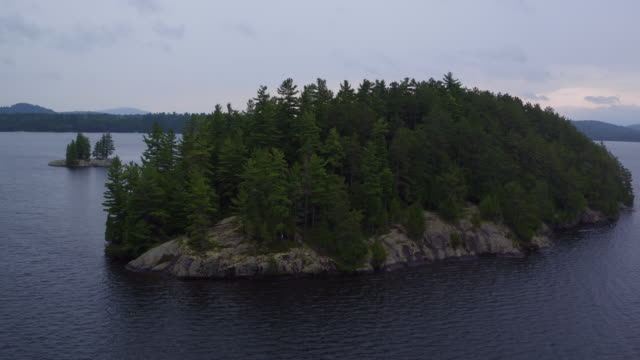 Aerial flying back from tight shot of small island in Saranac lake, midday