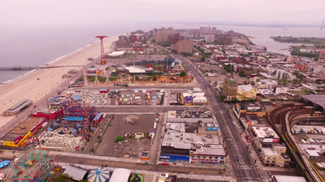 aerial flying back over coney island, beach and atlantic ocean in brooklyn, new york city - coney island stock-videos und b-roll-filmmaterial