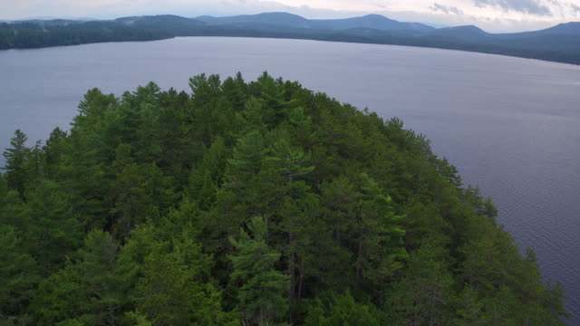 Aerial flying back over small island and water of Saranac lake, late afternoon