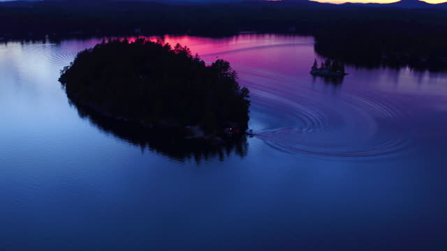 Aerial flying back over small island in Saranac lake at sunset with boat docking
