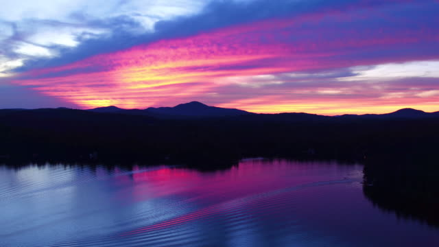 Aerial flying back over the water of Saranac lake at sunset