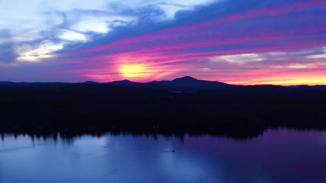 Aerial flying back over water of Saranac lake at sunset