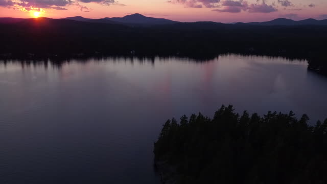 Aerial flying back over water of Saranac lake then small island at sunset