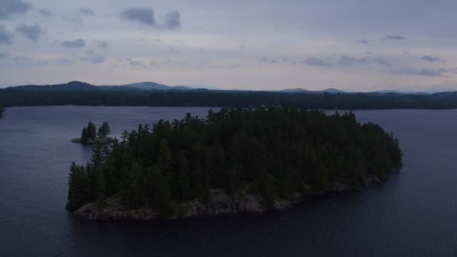 Aerial flying back past small island and water of Saranac lake, late afternoon