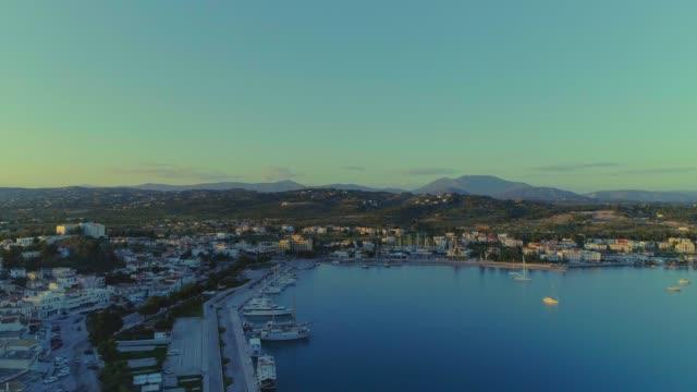 aerial - flying backwards above a small harbor at dusk - porto heli - porto cheli - greece - argolis - argolida - greece stock videos & royalty-free footage