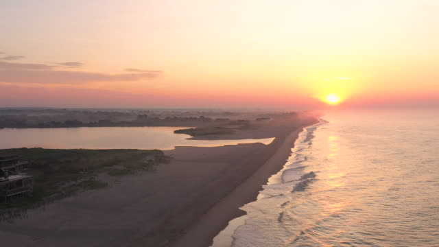 aerial flying backwards over beach in bridgehampton, ny at sunrise - long island video stock e b–roll