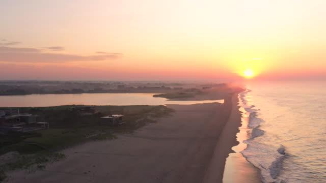 aerial flying backwards over beach in bridgehampton, ny at sunrise - bridgehampton stock videos & royalty-free footage
