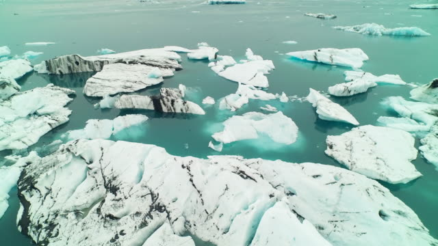 aerial flying backwards over jã¶kulsã¡rlã³n glacier lagoon in iceland - 風致地区点の映像素材/bロール