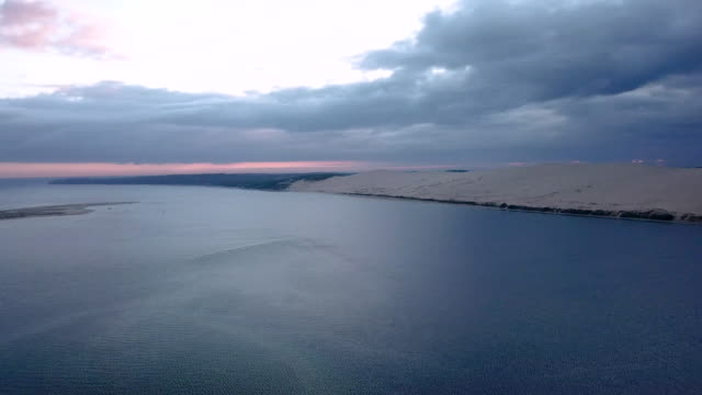 aerial flying backwards over the ocean away the dune of pilat at sunrise - arcachon stock videos & royalty-free footage