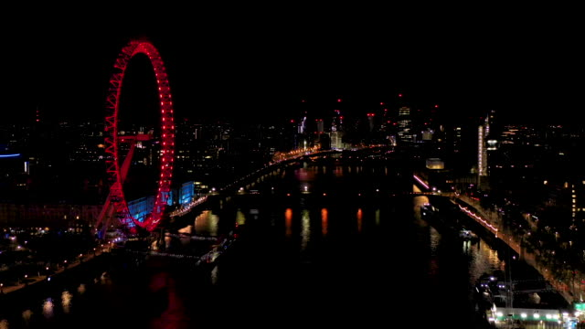 aerial flying backwards over the river thames in london uk at night, city full of lights - hungerford bridge stock videos & royalty-free footage