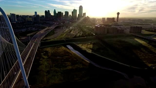 Aerial: Flying by Margaret Hunt Hill Bridge Sunrise Over Dallas Texas Skyline Cityscape Sun burst right above the horizon golden hour